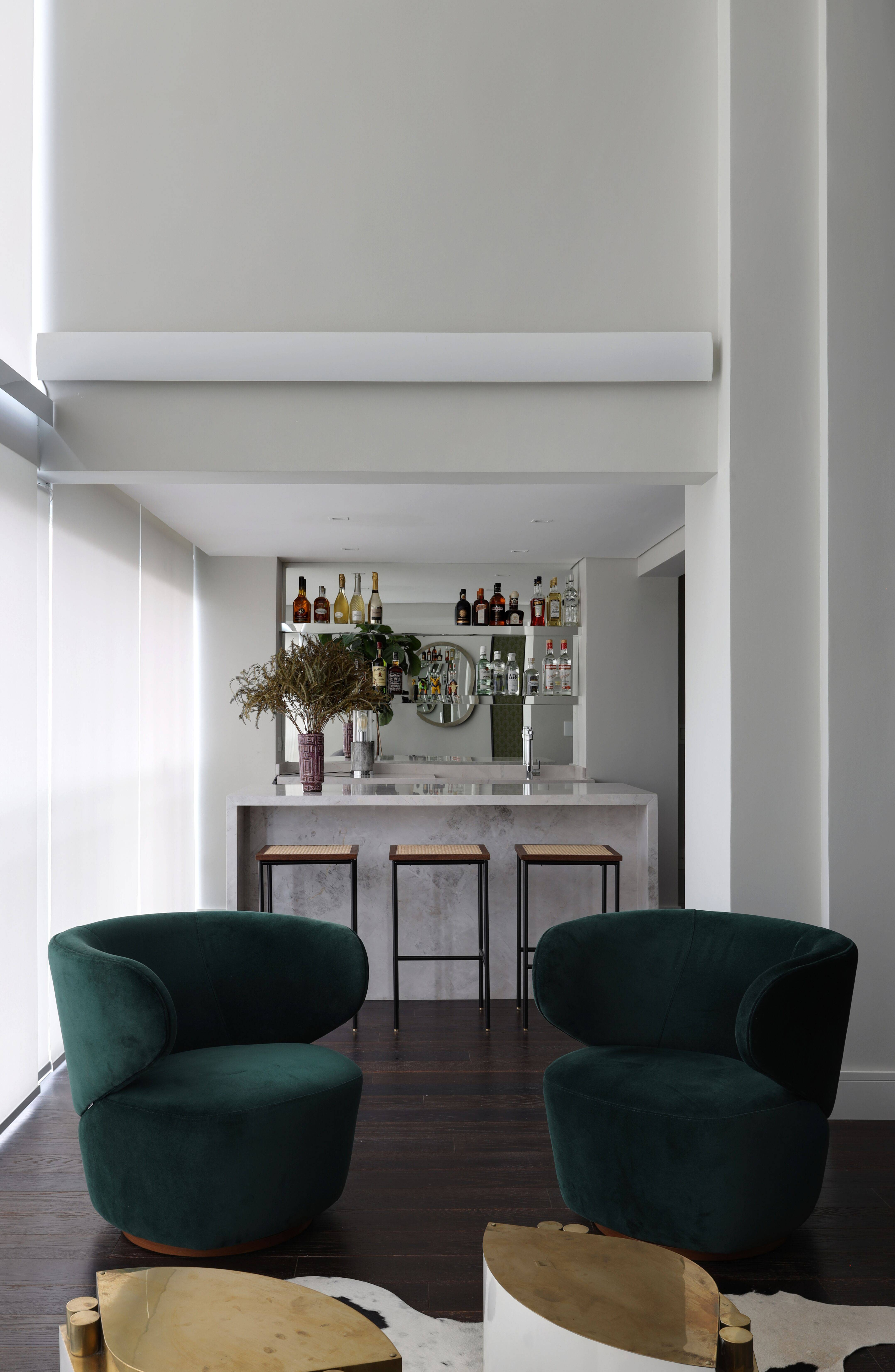 Um generoso bar foi montado com bancada de mármore e prateleiras espelhadas, em um lounge despojado com poltrona e mesas de apoio.