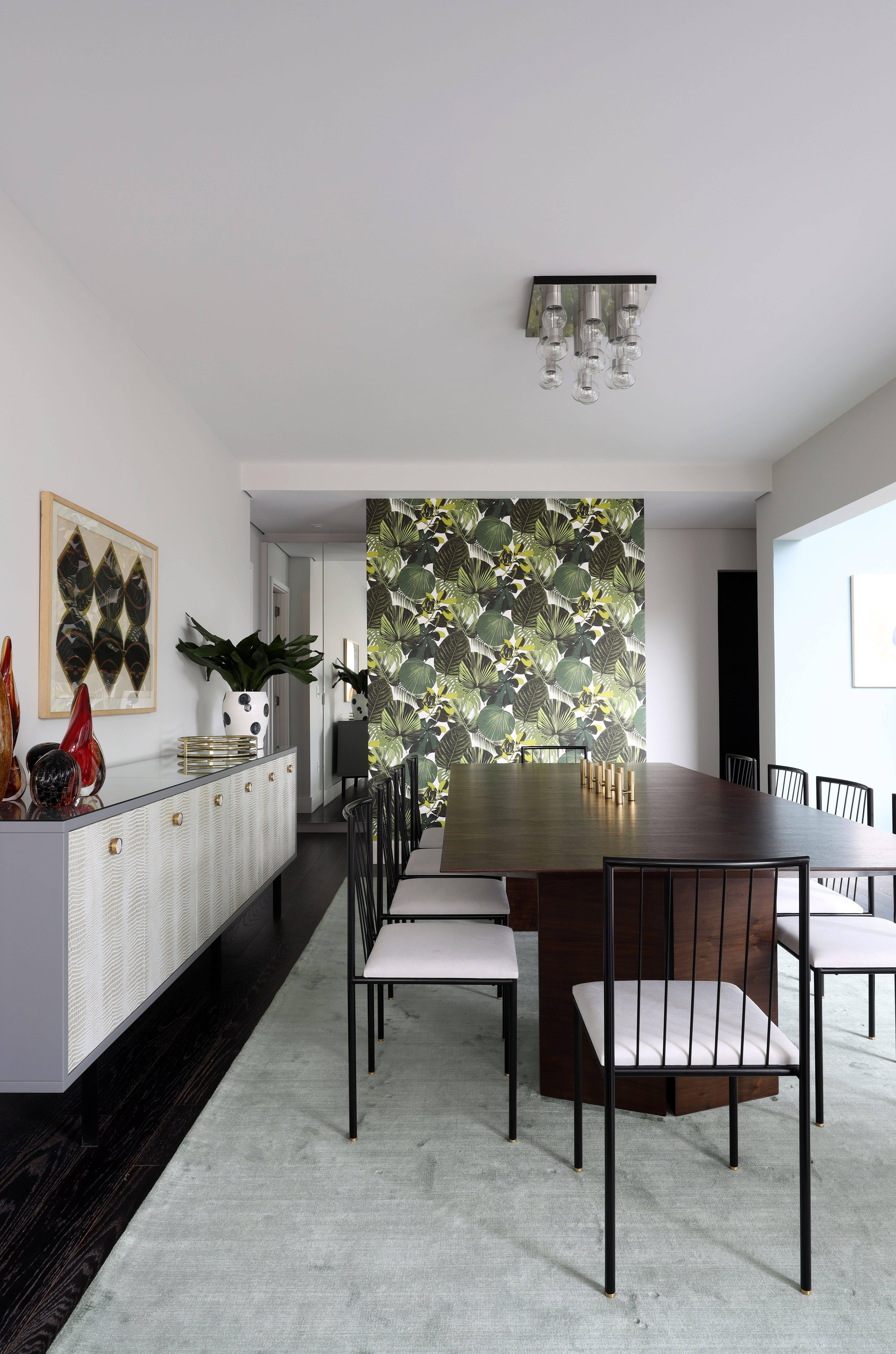O ar tropicalista que complementa a pegada vintage da decoração está presente no papel de parede da sala de jantar, utilizado também nos nichos da cozinha