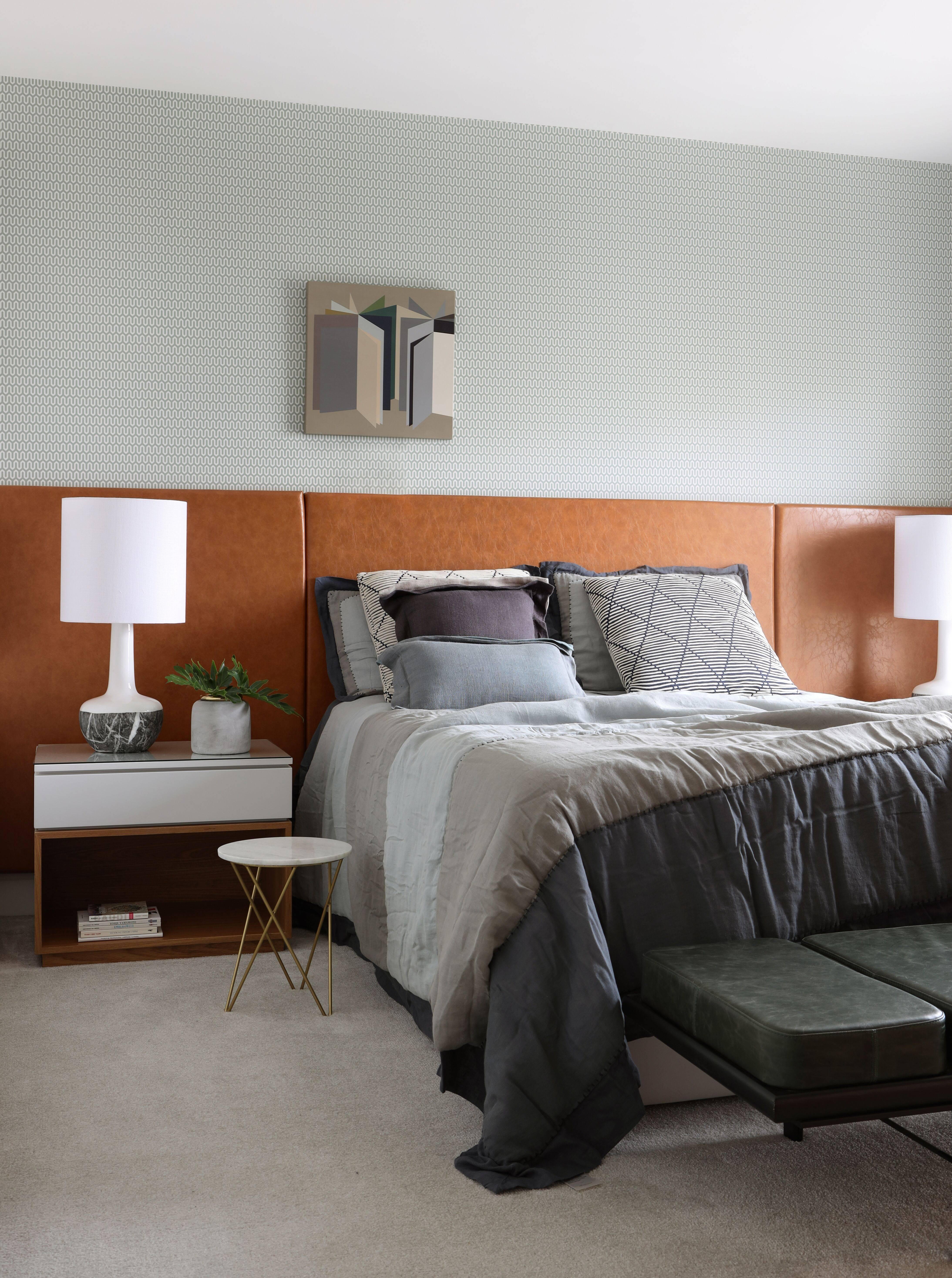 A pegada retrô também está presente no quarto do casal, com cabeceira de couro em laranja envelhecido e papel de parede escandinavo.