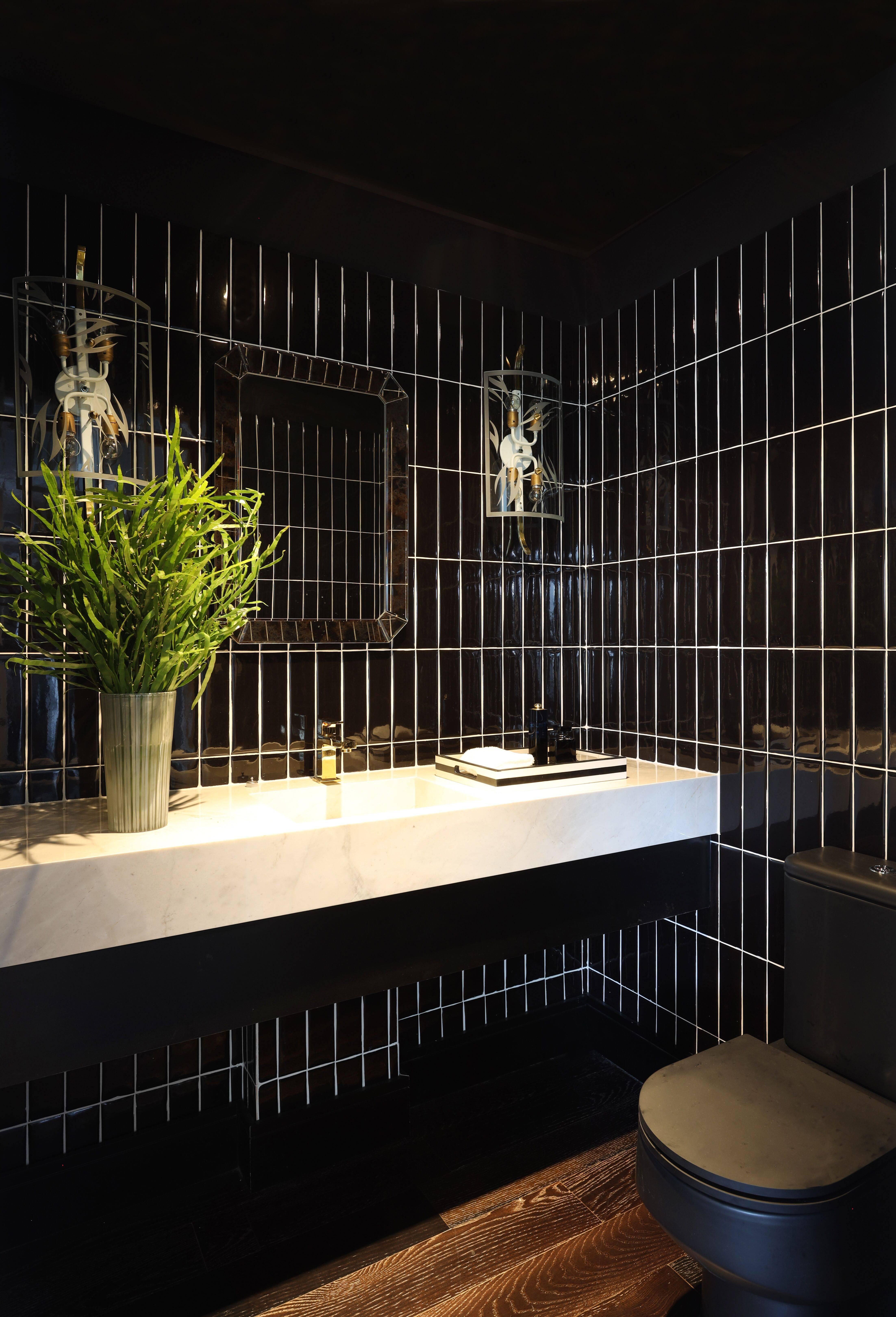No banheiro, azulejos pretos contrastam com a bancada em mármore branco.