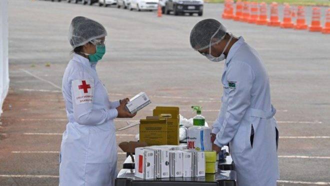 Profissionais de saúde se preparam para colher amostras para testes rápidos de coronavírus em drive-thru no estacionamento do Estádio Mané Garrincha, em Brasília