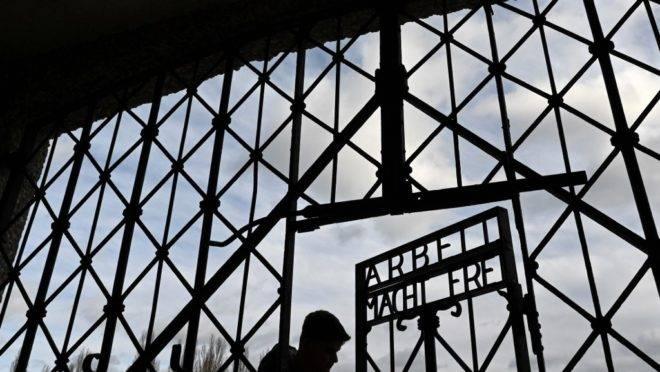 """Portão de entrada do antigo campo de concentração em Dachau, sul da Alemanha, com a inscrição """"O trabalho liberta"""""""