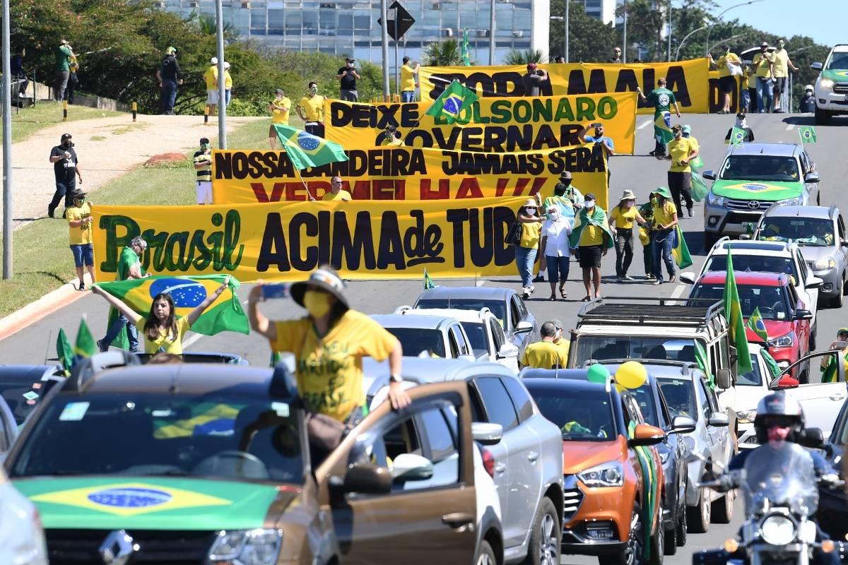 Apoiadores do presidente Jair Bolsonaro fizeram uma carreata em favor de seu governo com faixas contra o presidente da Câmara, Rodrigo Maia (DEM-RJ), e o Supremo Tribunal Federal (Foto: EVARISTO SA / AFP)