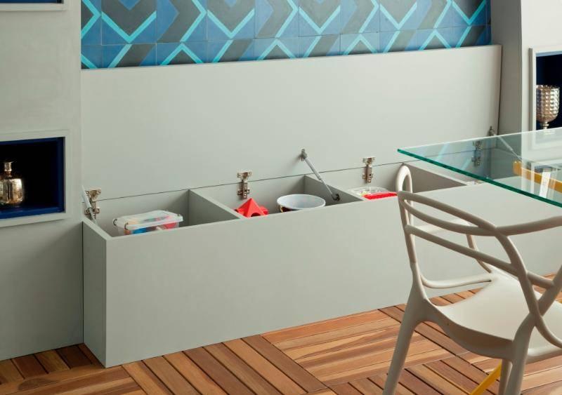 ). O banco abaixo dos ladrilhos hidráulicos é um suporte de mais lugares à mesa e de quebra guarda os brinquedos do filho do casal dono do apartamento