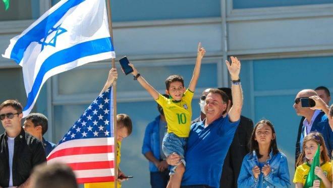 Bolsonaro acena para manifestantes a favor de seu governo em Brasília com as bandeiras de Israel e EUA ao fundo.