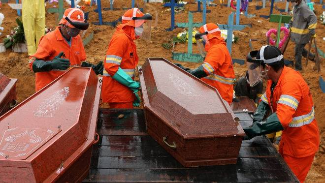 Coffins are unloaded to be buried in a mass grave at the Nossa Senhora cemetery in Manaus, Amazon state, Brazil on May 6, 2020. (Photo by MICHAEL DANTAS / AFP)