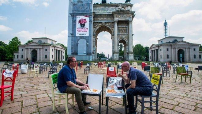 Donos de restaurante almoçam entre mesas vazias em frente ao monumento Arco della Pace, na Piazza Sempione, em Milão, em protesto contra o fechamento prolongado de seus negócios, no dia 6 de maio.