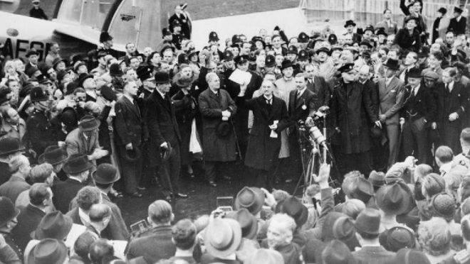 """Neville Chamberlain exibe a resolução assinada por ele e Adolf Hitler em Munique, em aeroporto de Londres, 30 de setembro de 1938. """"Teremos paz em nossos tempos"""""""
