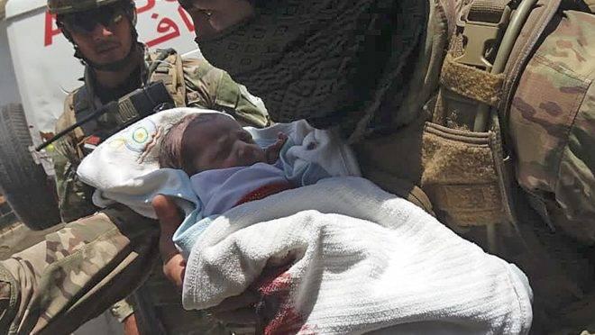 Membro de força de segurança retira bebê recém-nascido de hospital que foi alvo de ataque de atiradores em Cabul, 12 de maio