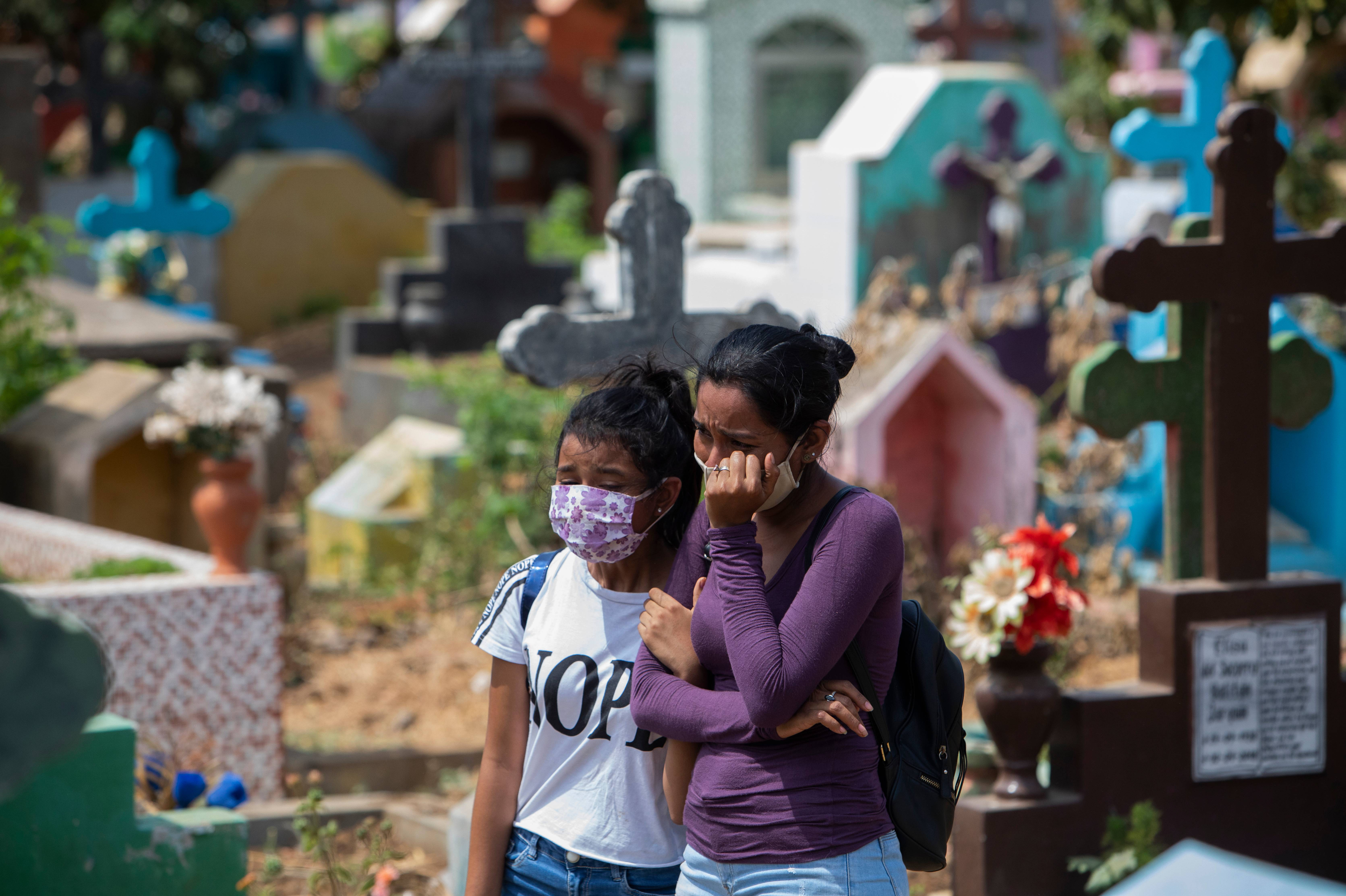 Relatives and friends of a mechanic called Roberto, who died at a hospital with symptoms of the novel coronavirus, COVID-19 and did not have a wake before his burial, cry at the Milagro de Dios Cemetery in Managua, on May 9, 2020. – The novel coronavirus has killed at least 276,435 people worldwide since the outbreak first emerged in China last December, according to a tally from official sources compiled by AFP at 1900 GMT on Saturday (Photo by Inti OCON / AFP)