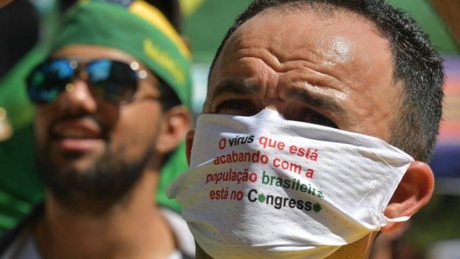 Manifestante participa de ato público, em Brasília, usando máscara com crítica ao Congresso.