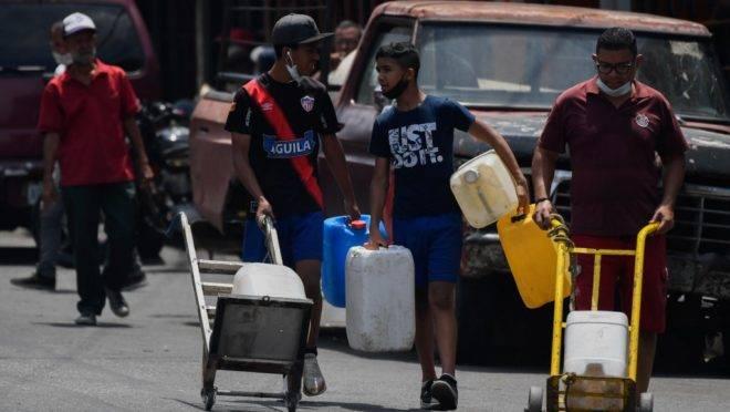 Pessoas transportam água em Caracas, Venezuela, durante a pandemia de coronavírus, 19 de maio de 2020