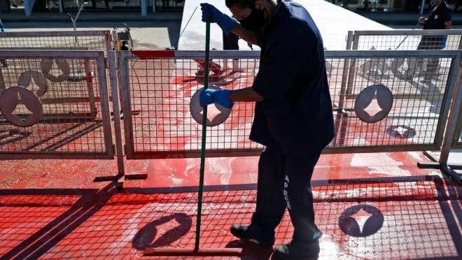 Funcionário limpa tinta vermelha que foi jogada por manifestante em frente ao Palácio do Planalto