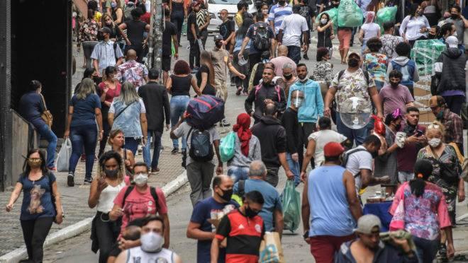 Pessoas andando pelas ruas de comércio popular em São Paulo após a reabertura: número de infectados no Brasil deve bater 1 milhão de casos de coronavírus esta sexta.