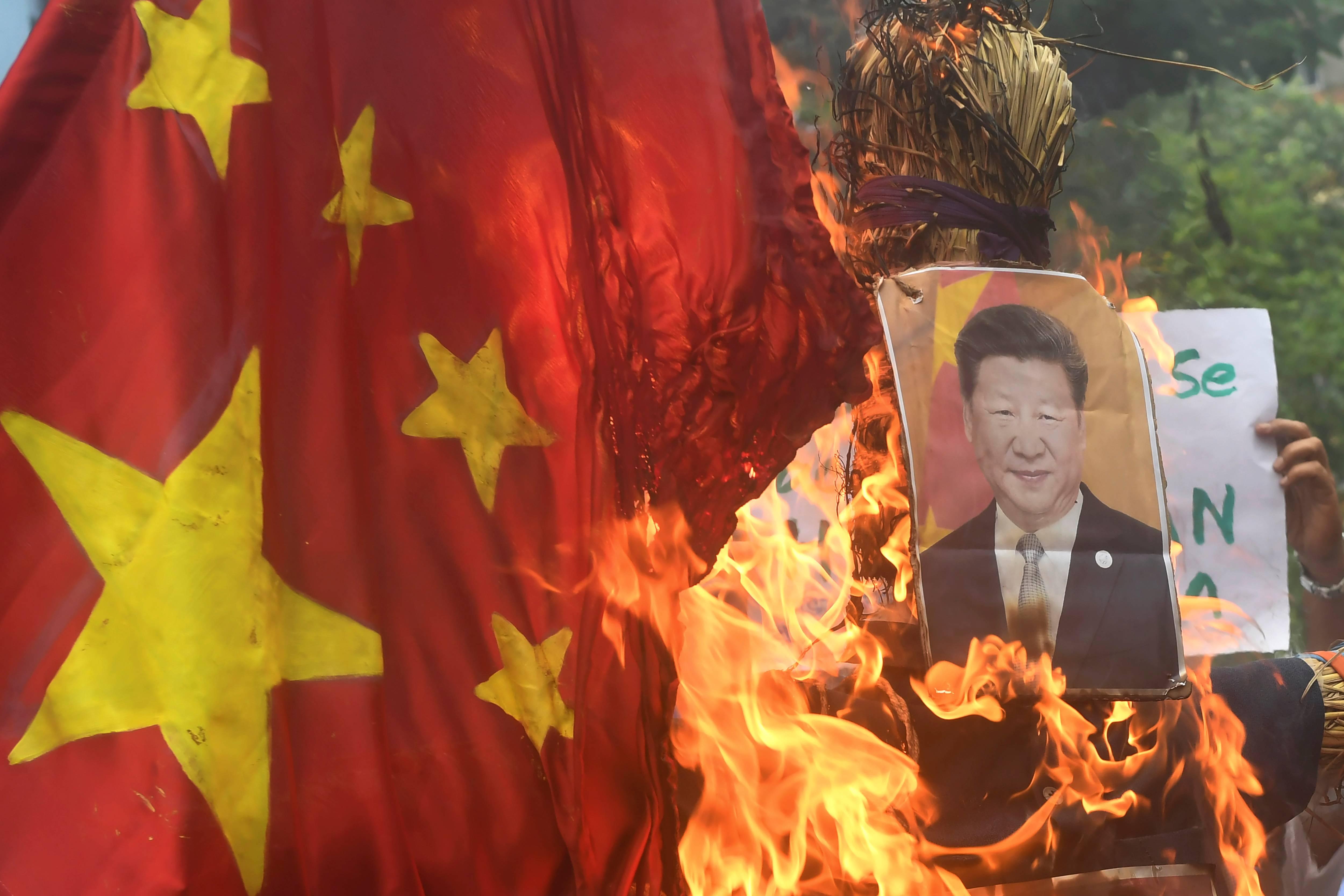 Manifestantes queimam uma efígie do presidente chinês Xi Jinping e da bandeira nacional da China durante uma manifestação anti-China em Calcutá, 18 de junho de 2020 | FOTO: Dibyangshu SARKAR/AFP