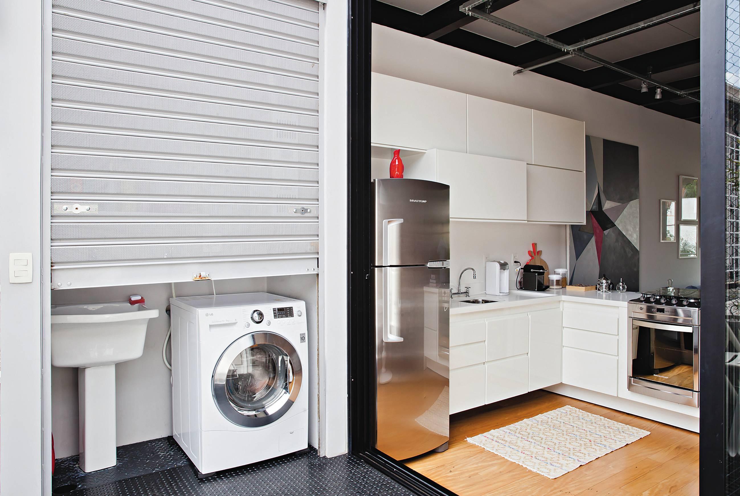 Nessa residência compacta projetada pelo SuperLimão Studio, uma microlavanderia fica escondida atrás de um portão horizontal que funciona como um armário e pode ser completamente fechado. Foto: Maíra Acayaba
