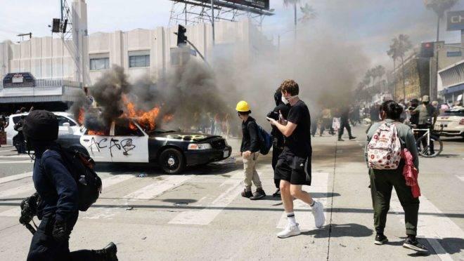 Veículo da polícia de Los Angeles queima em Los Angeles, Califórnia, depois de ser incendiado por manifestantes após a morte de George Floyd em 30 de maio de 2020.