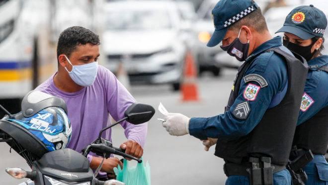 Policial militar faz inspeção de documentos de motoqueiro em Belém do Pará, durante vigência do lockdown que restringiu a circulação de pessoas nas ruas.