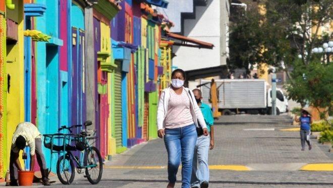 Pessoas usando máscara de proteção caminham pelas ruas de Maracaibo, segunda maior cidade da Venezuela (Luis Bravo/AFP).