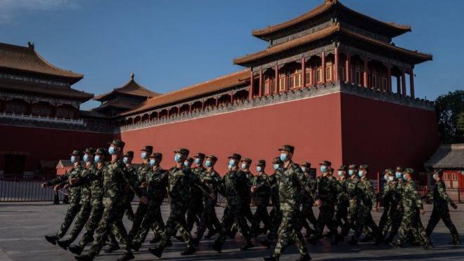 Policiais paramilitares com máscaras marcham em frente à entrada da Cidade Proibida em Pequim em 19 de maio de 2020.