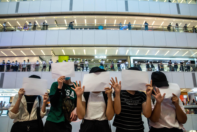 Manifestantes seguram papéis em branco durante uma manifestação em um shopping em Hong Kong em 6 de julho de 2020 | Foto: ISAAC LAWRENCE / AFP