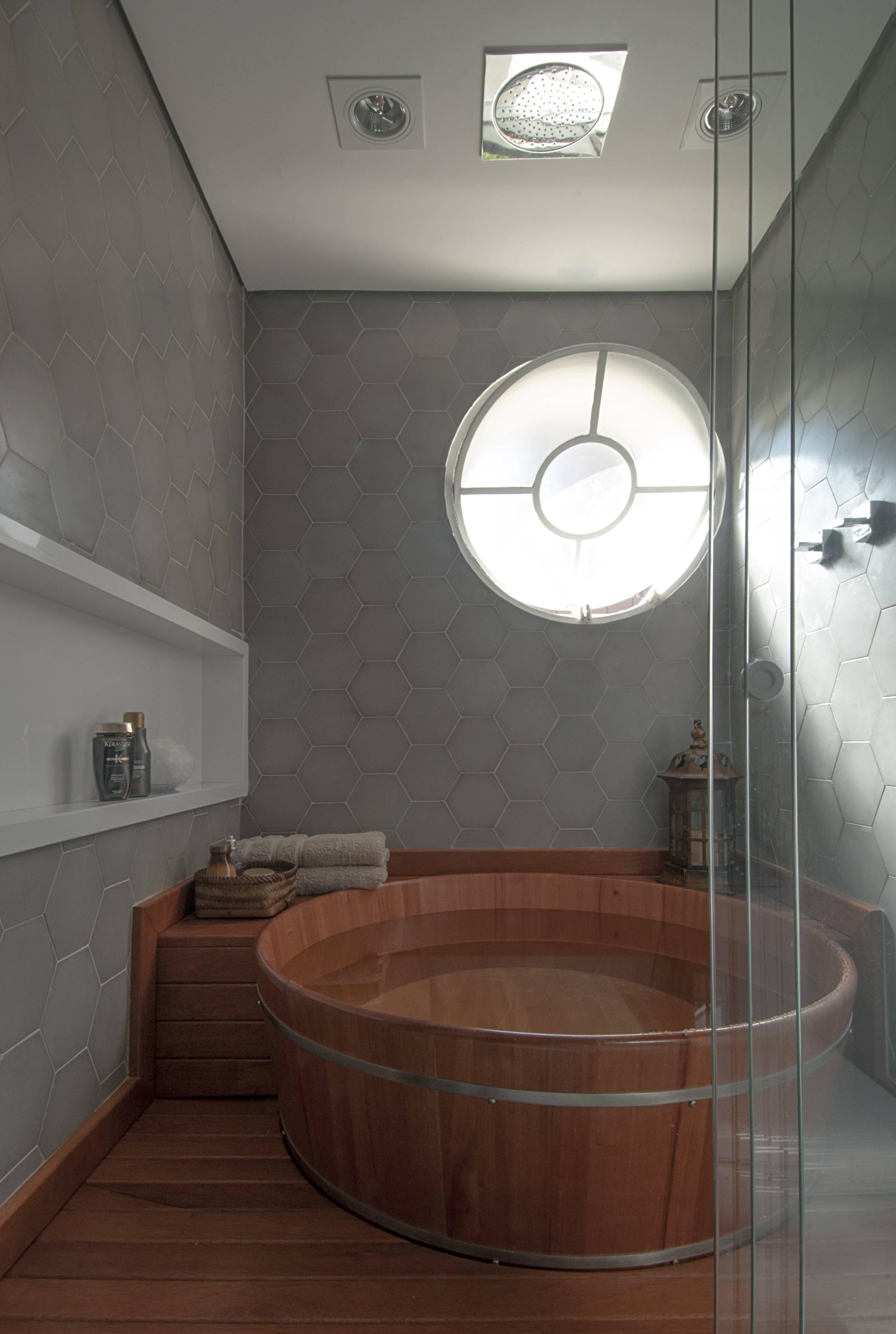 O chuveiro de teto foi posicionado no centro do ofurô que, por sua vez, está no centro da área molhada. Revestimento cimentício contrasta com a madeira, que aquece o espaço.