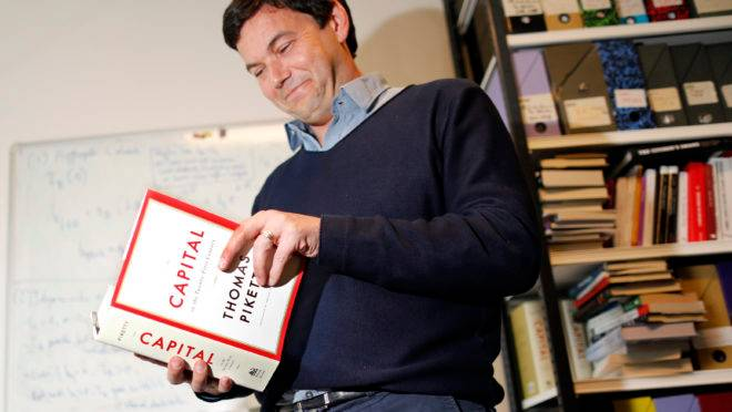 "French economist and academic Thomas Piketty, poses in his book-lined office at the French School for Advanced Studies in the Social Sciences (EHESS), in Paris May 12, 2014. The 43-year-old Piketty's book ""Capital in the Twenty-First Century"" has attracted praise and invective alike on its way to the top of the Amazon.com books best-seller list. Picture taken May 12, 2014.  REUTERS/Charles Platiau (FRANCE – Tags: POLITICS SOCIETY BUSINESS EDUCATION) – RTR3OZ0F"
