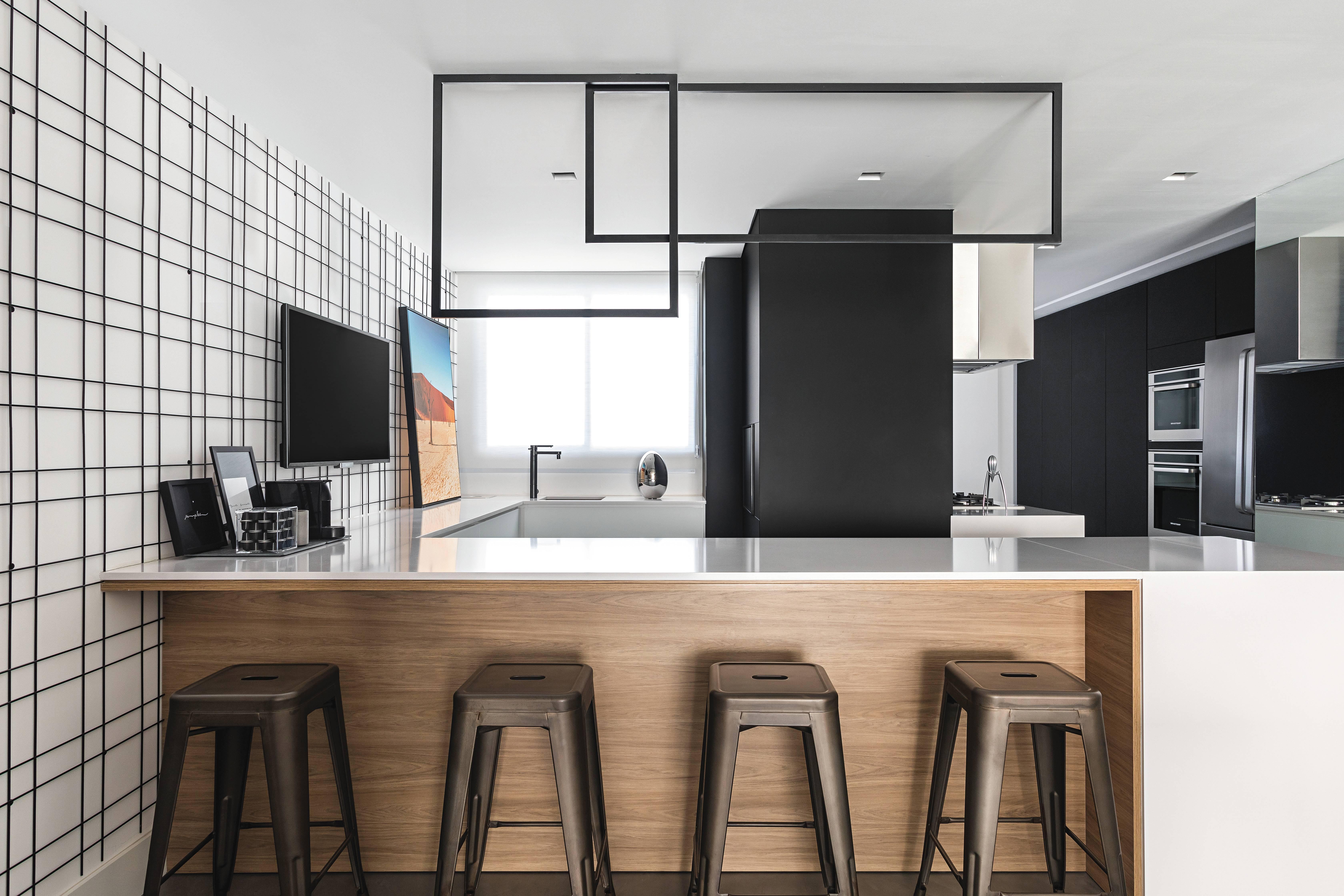 O aramado que reveste uma das paredes do chão ao teto é ponto de destaque na cozinha integrada com a churrasqueira. Foto: Eduardo Macarios