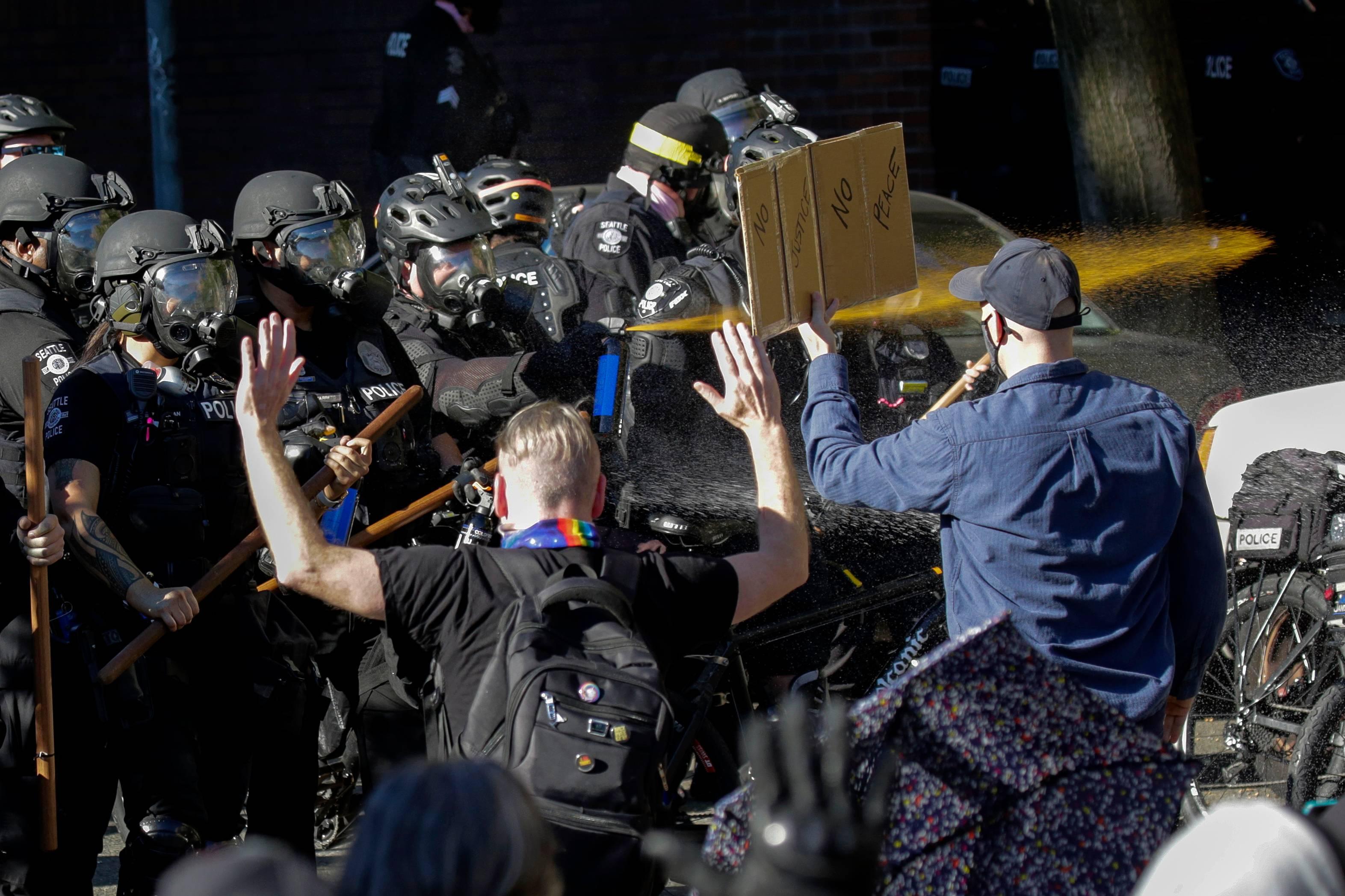 Policiais lançam spray de pimenta em manifestantes, em Seattle, em 25 de julho de 2020   Foto: Jason Redmond/ AFP