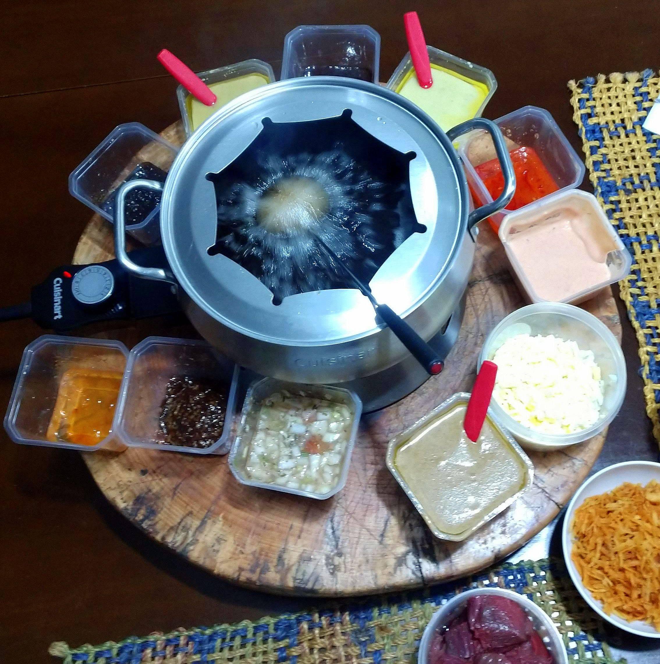 Carne fritando no óleo e 11 opções de acompanhamento em volta. É o delivery de fondue do Pachá.