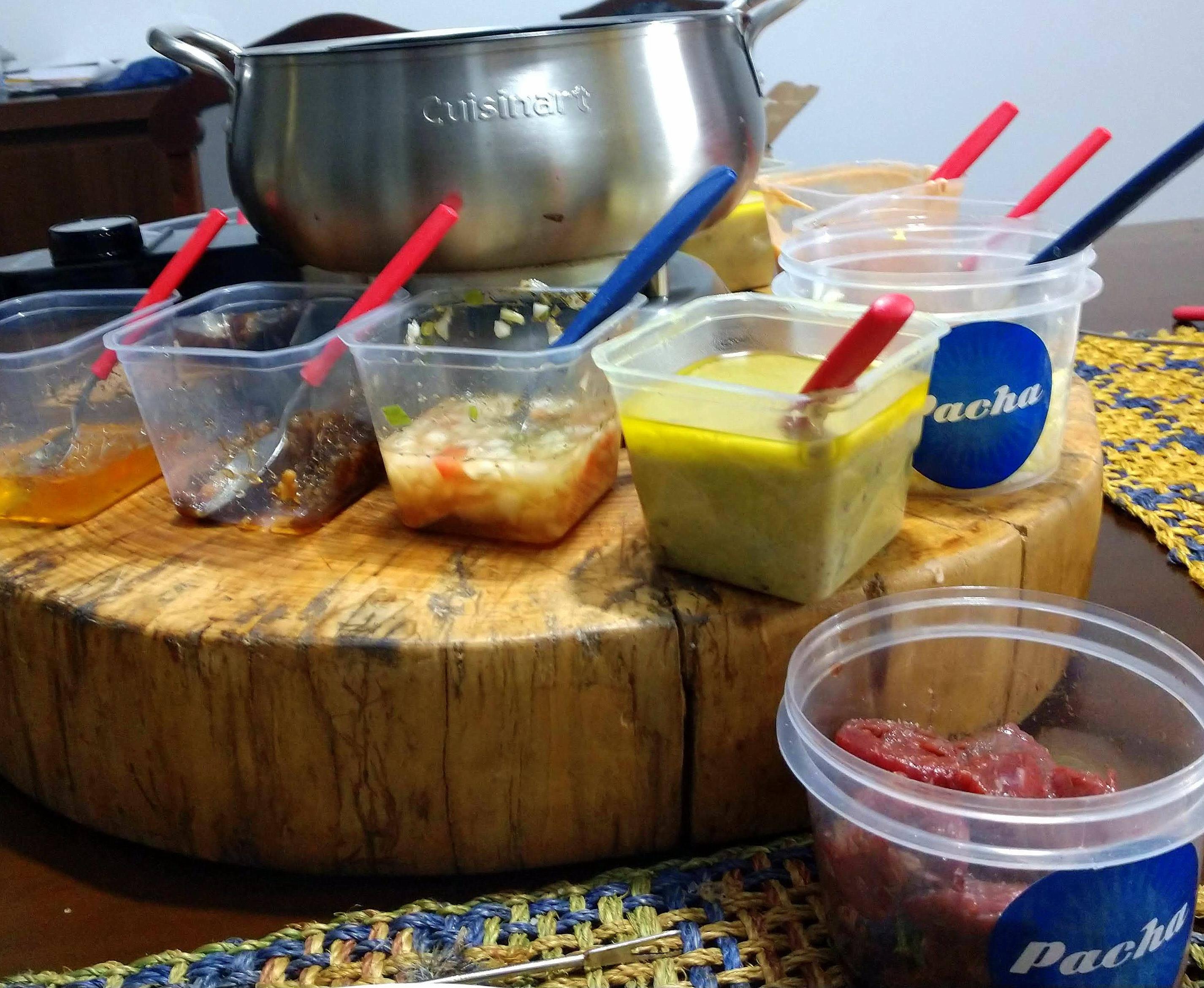 Óleo quente na panela, molhos e  acompanhamentos distribuídos em volta... agora é só começar a comer.