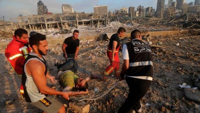 Bombeiros carregam homem ferido em local perto de onde ocorreram as explosões em Beirute em 4 de agosto de 2020.