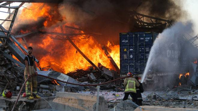 Bombeiros tentam apagar o fogo após explosões no porto de Beirute | Foto: STR/AFP