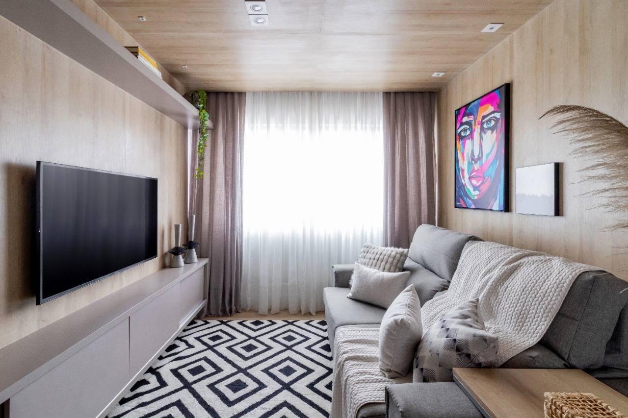 """Sala foi revestida com painéis em madeira e piso vinílico que colocaram o cômodo dentro de uma """"caixa"""". Foto: Divulgação/Flávia Franco"""