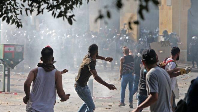 Manifestantes lançam pedras contra as forças de segurança do Líbano durante confrontos no centro de Beirute, neste sábado (8).