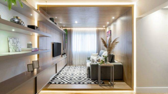 """Sala foi revestida com painéis em madeira e piso vinílico que colocaram o cômodo dentro de uma """"caixa""""."""