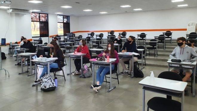 Imagem mostra sala de aula de colégio particular em Foz do Iguaçu com poucos alunos usando máscara e em distanciamento social, dentro do protocolo sanitário contra a disseminação do coronavírus.