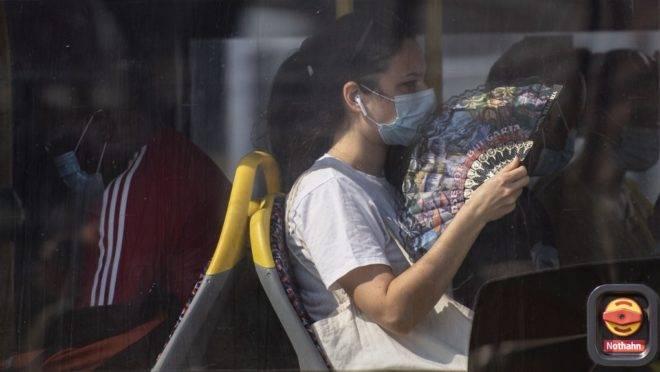Uma passageira vestindo uma máscara usa um leque para se aliviar do calor em um ônibus de Berlim, em 15 de agosto de 2020.