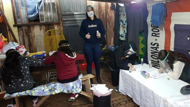 A líder comunitária da favela Primeiro de Maio, no bairro Cidade Industrial de Curitiba, recebe crianças na garagem de casa para ajudar nas tarefas escolares.