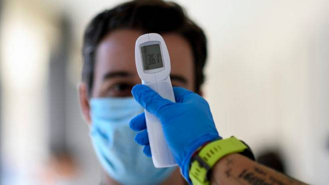 """A healthcare worker takes the temperature to a man at a temporary testing centre for the novel coronavirus in Madrid on August 17, 2020. – Just seven weeks after bringing its first coronavirus wave under control, experts say Spain is once again in a """"critical"""" situation with the worst infection rate in Western Europe. (Photo by OSCAR DEL POZO / AFP)"""