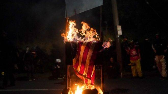 Bandeira norte-americana é incendiada por manifestantes em Portland.