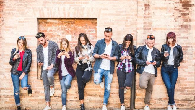 Jovens usam celular encostados em uma parede.