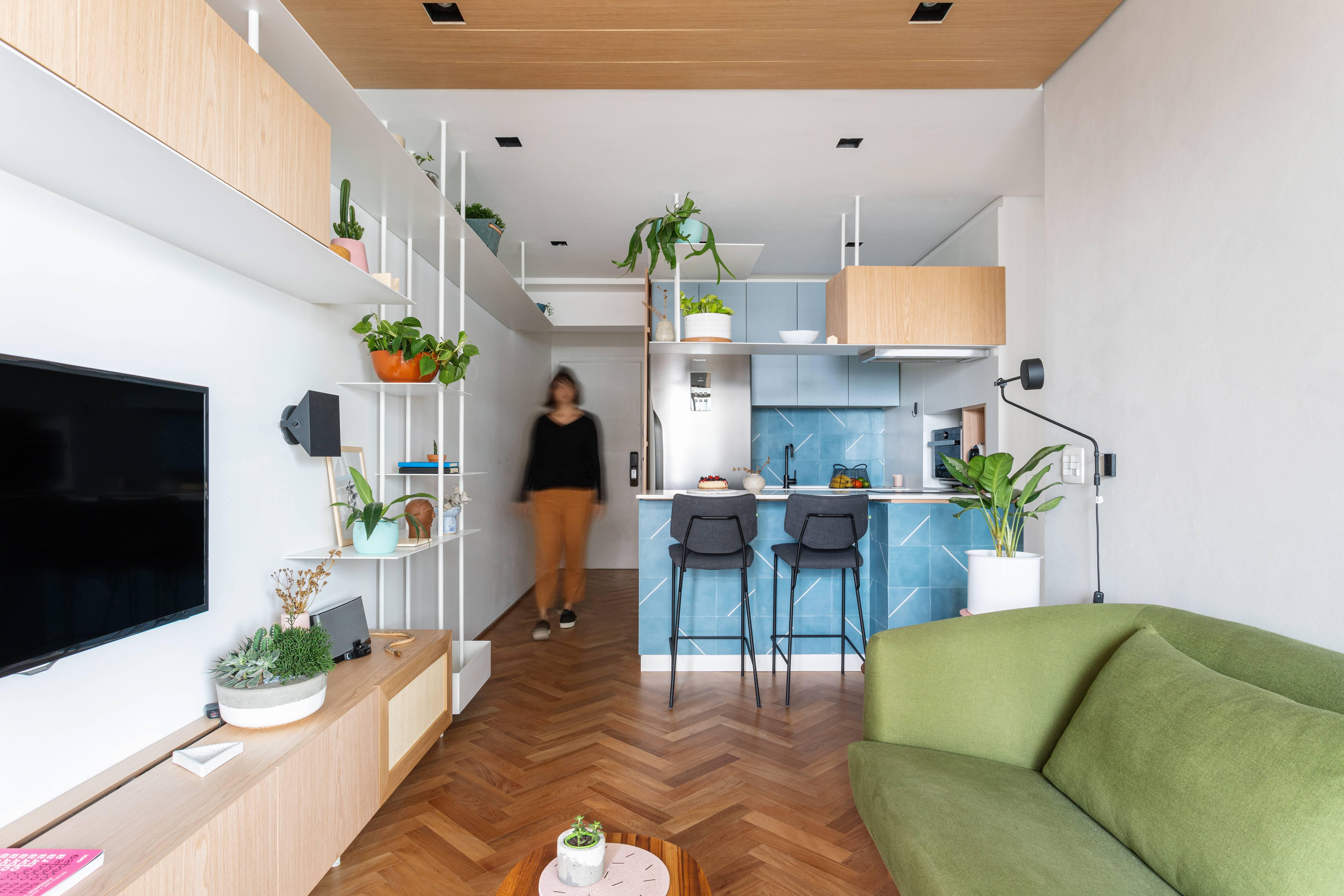 No projeto do Estúdio Bra, estante avança da sala até o hall e a cozinha do apartamento Góes. Foto: Divulgação