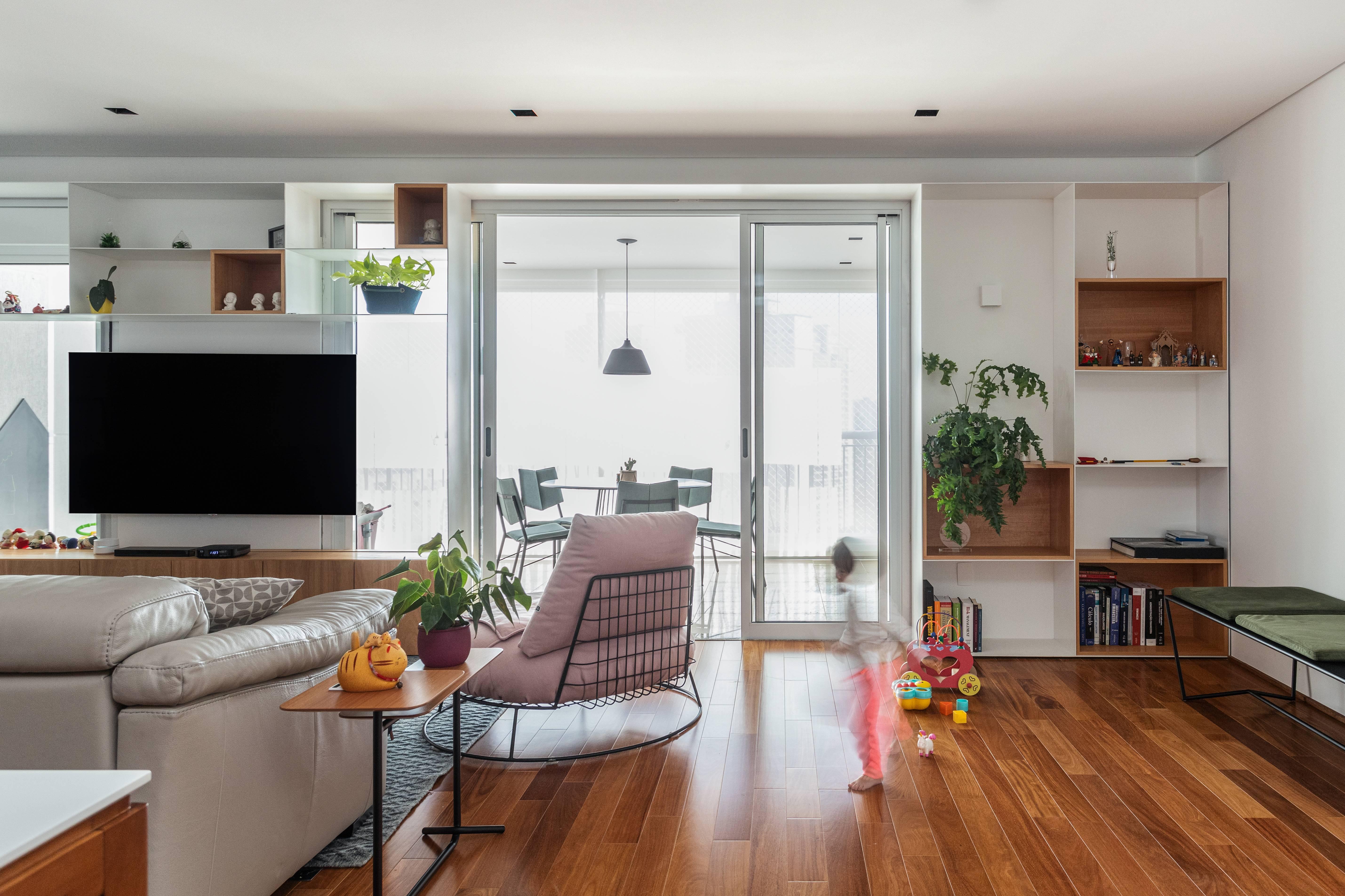 No apartamento Taka, do Estudio Bra, leveza da estante, aliada à cor branca, faz com que ela quase se funda à parede. Foto: Divulgação
