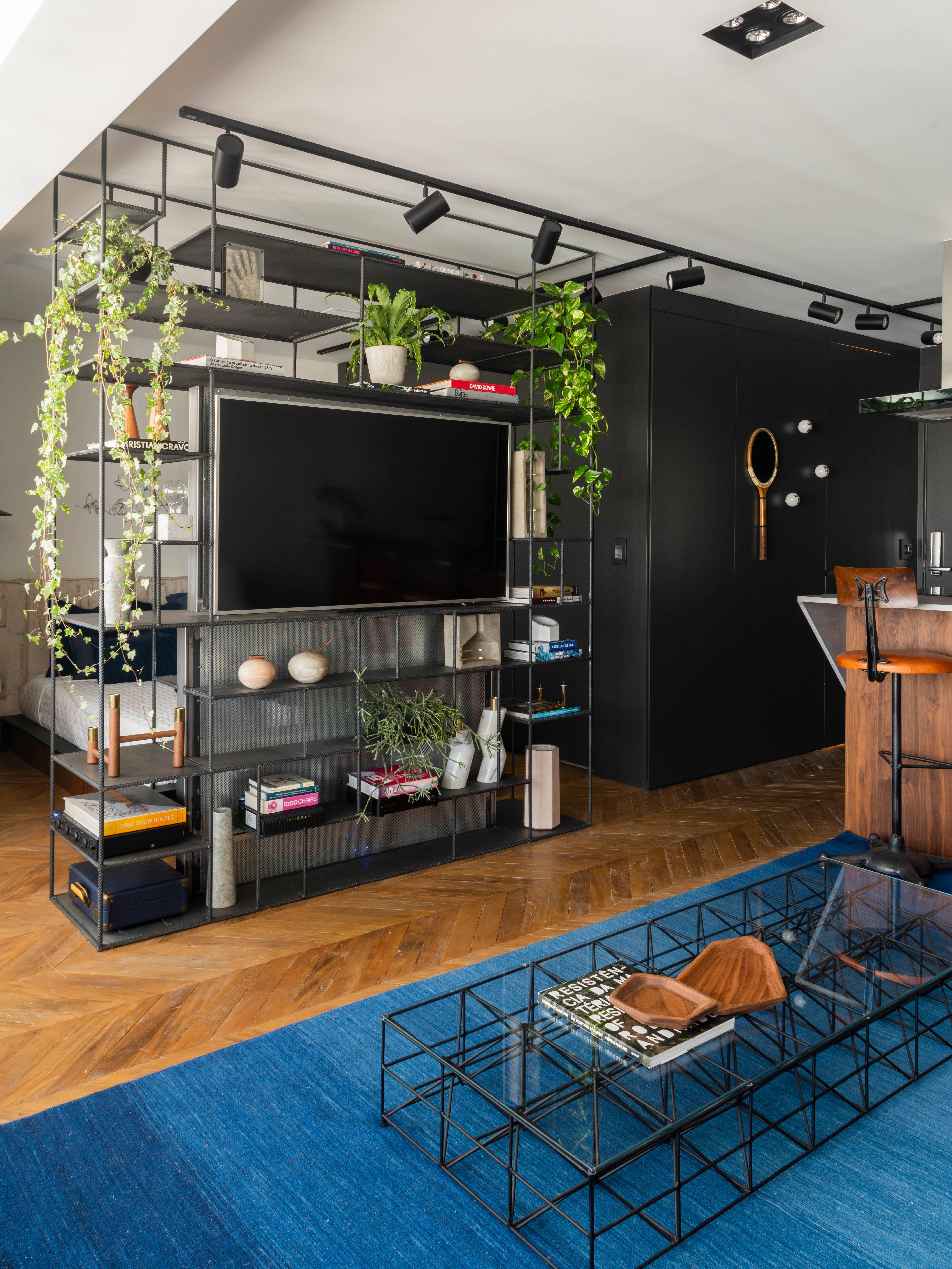 Em metal, estante delimita e integra os ambientes, servindo ao living e ao dormitório no projeto da Rua 141 e de Rafael Zalc. Foto: Divulgação