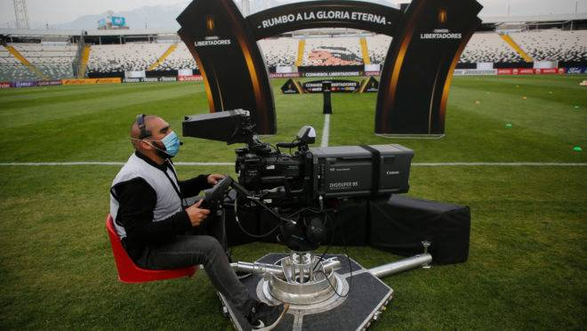 A cameraman gets ready before the start of the closed-door Copa Libertadores group phase football match between Chile's Colo Colo and Uruguay's Penarol, at the Monumental stadium in Santiago, on September 15, 2020, amid the COVID-19 novel coronavirus pandemic. (Photo by Marcelo HERNANDEZ / POOL / AFP)
