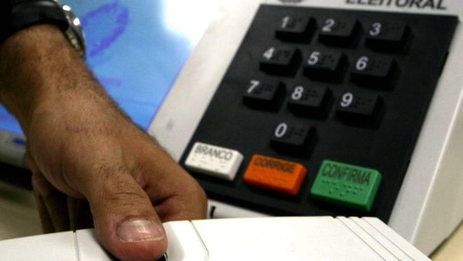 Mão de eleitor faz biometria com a urna eletrônica ao fundo.
