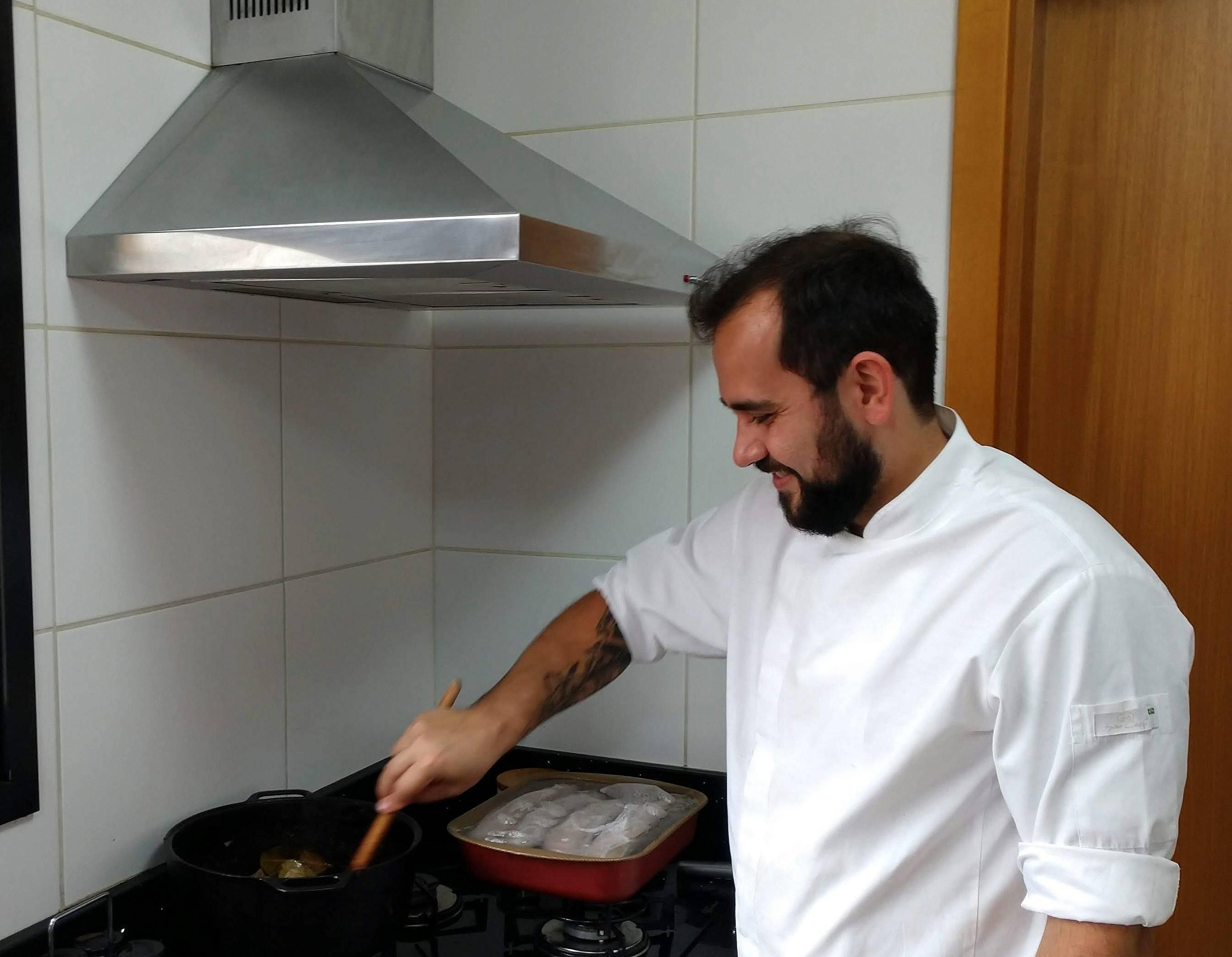 Tristão cozinhando em seu pequeno fogão caseiro, de quatro bocas.