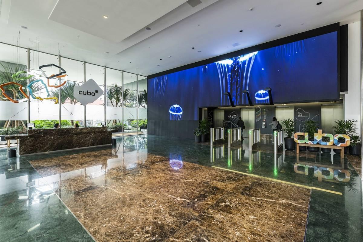 Inaugurado em 2018 em São Paulo, os espaços brincam com cores e diferentes materiais que se afastam da clássica linguagem corporativa. Videowall na entrada do prédio é destaque do projeto
