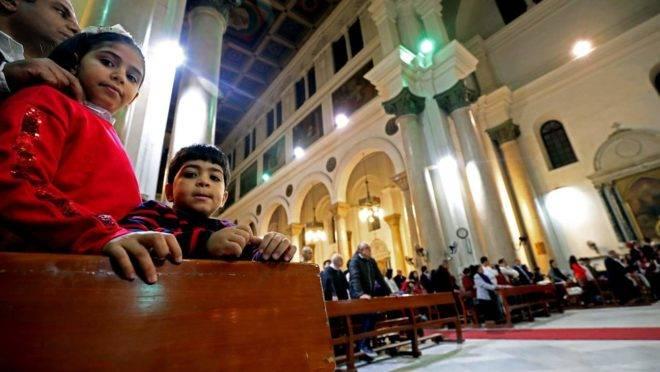 Crianças assistem enquanto os fiéis participam da missa da meia-noite na véspera de Natal na Igreja Católica Romana de São José, na capital egípcia Cairo, no distrito central da cidade, em 24 de dezembro de 2019: Egito é um dos países onde os cristão são mais perseguidos por causa de sua fé